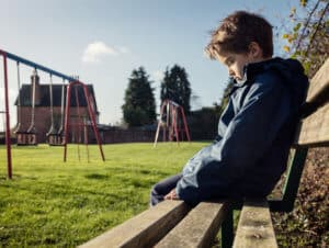 Young Boy Sitting on Park Bench Alone - Child Neglect and Abuse - Martin, Harding & Mazzotti 1800law1010